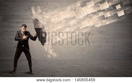 Business man protecting with umbrella against wind of papers concept