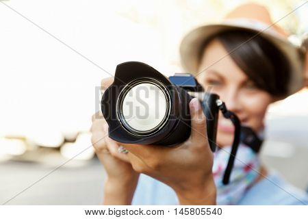 Outdoor summer smiling lifestyle portrait of pretty young woman with camera