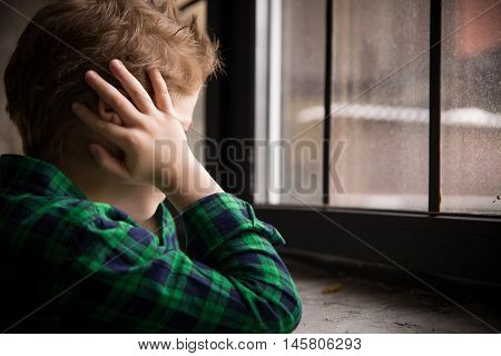 Little boy standing behind the window in sad mood. Sad Teenager looking in the Window and closing his ears with hands. Unhappy child in a plaid shirt. Alone at home. Upset.