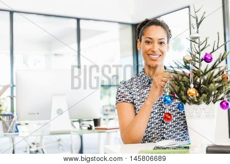 Portrait of smiling afro-american office worker decorating christmas tree in offfice