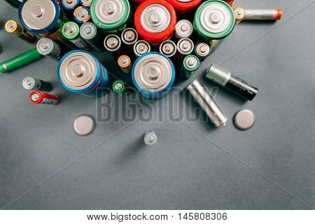 Top view on portable batteries on gray background, free space. Colorful energy composition, variety of different kinds of accumulators, copy space