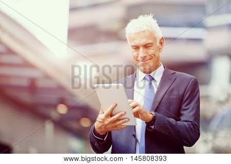 Senior businessman holding touchpad