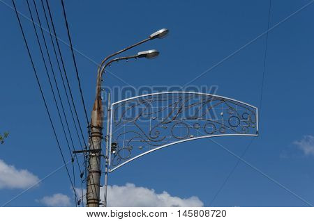 Streetlight with ornament in the form of flowers against the background of the blue sky