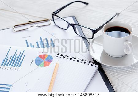 workplace economist at bright new office table with diagram and coffe cup