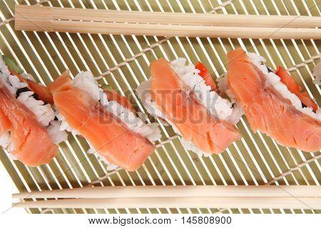 fresh japan onigiri inside out sashimi sushi on wooden bamboo mat with sticks isolated on white background