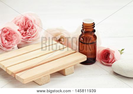Rose essential oil bottle, fresh pink flowers, wooden surface for product display. Holistic beauty care. Creamy pastel tones, soft focus.