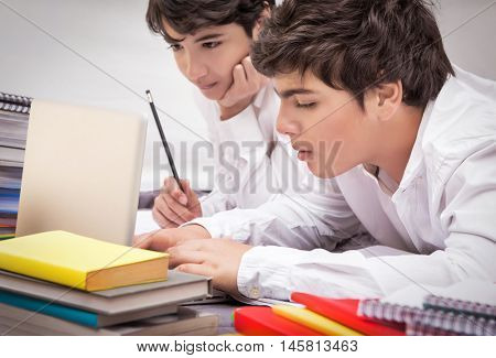Two classmates doing homework together at home, resolving difficult task, searching information on internet, preparation to exams, with pleasure studying at school