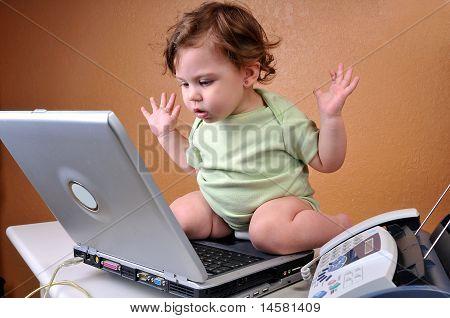Baby looking at laptop baffled