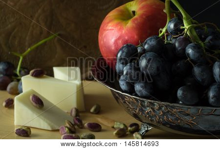 Antique Fruit Bowl With Cluster Of Grapes, Apple With Pieces Vegan Cheese And Pistachios.