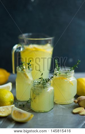 Lemonade drink. Lemonade in the jug and glass jars with lemons, ginger and thyme