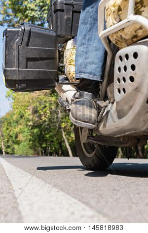 Motorcyclist's boot on the road, color image