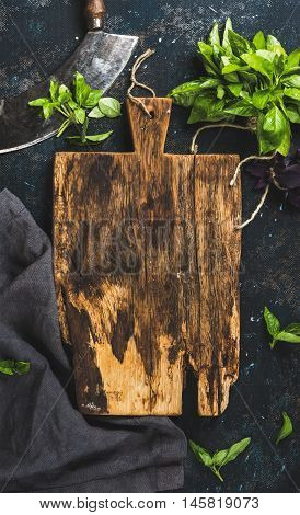 Fresh green basil leaves with herb chopper knife, rustic cutting board in center over grunge dark blue plywood texture. Top view, copy space, vertical composition