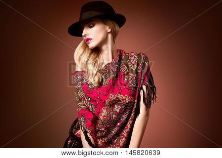 Fall Fashion. Model Woman in Autumn Fashion Shawl, Stylish Trendy Hat. Playful Blonde girl with Wavy hair, fashion Ethnic Glamour Headscarf. Fall Autumn Winter. Makeup. Fashion Pose. Creative Vintage