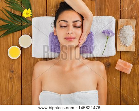 Head massage in aroma spa. Young woman in wellness center. Professional cosmetologist make procedure to beautiful indian girl in beauty parlor. Top view with eyes closed, laying on wood
