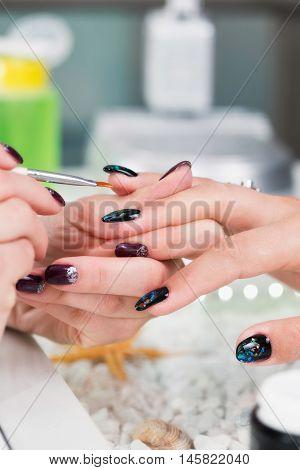 Designing fingernails in nail salon, color image