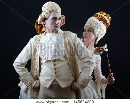 actor and actress in period costume and wigs on a dark background