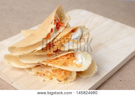 Thai pancake it is delicious snacks on wood background Kind of Thai sweetmeat or Kanom Buang - Thai Style Crispy Tart or Thai sweetmeat with wood cutting board on wood background poster