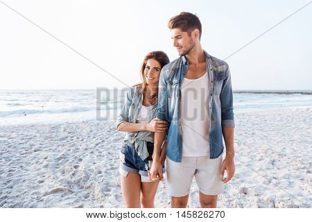 Beautiful young couple holding hands and walking at the beach