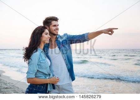 Happy young couple looking and pointing away on the beach