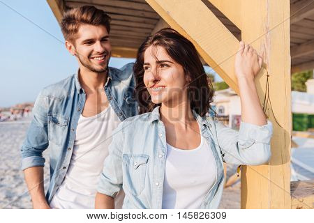 Beautiful young smiling couple in love standing at the beach house