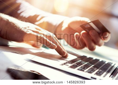 Closeup Man Holding Hand Credit Card.Businessman Use Laptop Online Payments Shopping.Guy Typing Keyboard Notebook Name Numbers Plastic Debit Kard Holder.Flares, Blurred Background