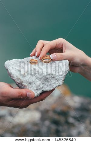Wedding Rings In Hands Of Bride On Stone Background