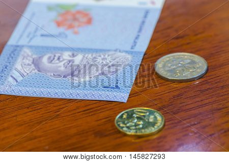 Malaysian ringgit coins and Malaysian ringgit notes on wood Table