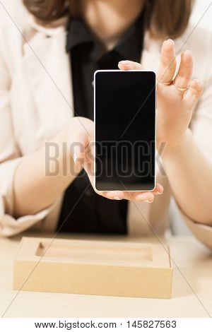 Unrecognizable woman shows new model of smartphone with blank screen. Modern technology presentation. Recent phone sample in female hands