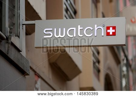 BASEL, SWITZERLAND - JULY 06, 2016: Sign of Swatch on building facade. Swatch is a Swiss watch making company.