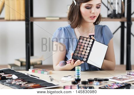 Cosmetics consult tells about eyeshadows palette. Young woman holding colorful eye cosmetics swatch. Makeup, beauty, fashion concept