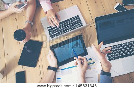 Young Business Team Brainstorming Meeting Room Process.Coworkers Startup Marketing Project.Creative People Making Great Work Decisions Wood Table.Tablet Laptop Graphs Diagram Screen.Blurred Background