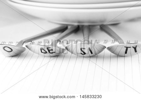 Spoons with reflection of the word obesity in black and white