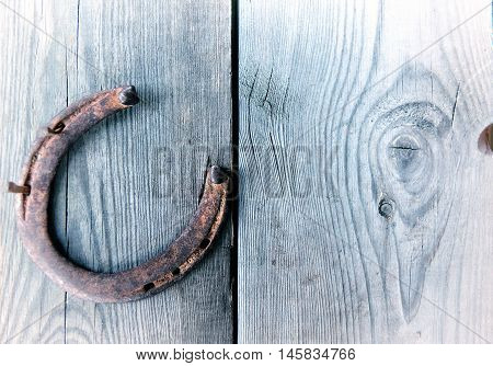 Old rusty horseshoe on vintage wooden board- rustic scene in a country style. Old iron Horseshoe - good luck symbol and mascot of well-being in a village house in Western culture.