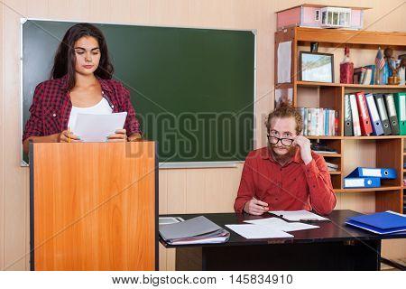 Young Girl Student Prepare Report Seminar Standing At Platform In Classroom, Professor Listen High School Education