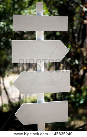 White wooden sign post with multiple signs.
