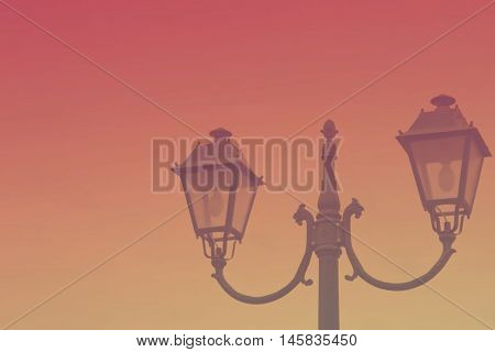 Vintage streetlight on sunset background. Toned image