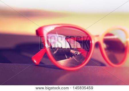 Red sunglasses on the car dashboard with reflection of the sun. Soft focus. Toned image. Blurred effect