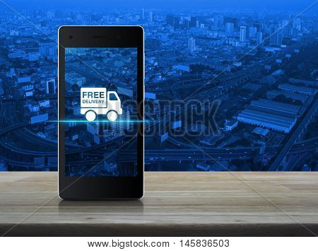 Free delivery truck icon on modern smart phone screen on wooden table in front of aerial view of cityscape expressway and highway Transportation business concept