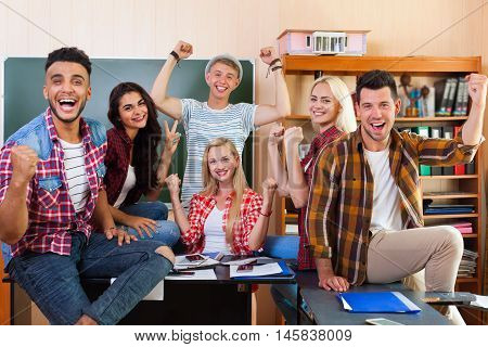 Happy Smiling Student High School Group In University Classroom, Successful Excited Young People Cheerful Facial Expression Hold Fist Raised Hands Up