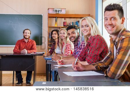 Smiling Student High School Group Write Test Looking At Camera Professor, People Sit Desk University Classroom