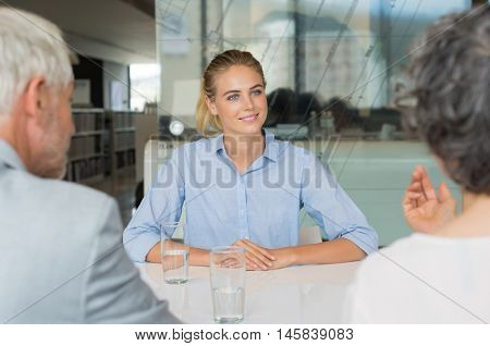 Portrait of woman sitting in front of manager and senior leader during a job interview. Senior business people in conversation with a young business woman. Recruiter checking the candidate.