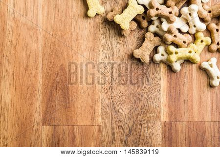 Dog food shaped like bones on wooden table. Top view.