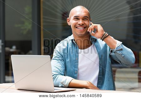 Smiling man in a conversation over phone outdoor. Happy african guy talking on mobile phone and looking away. Smiling student in casual talking on cell phone with computer on table.