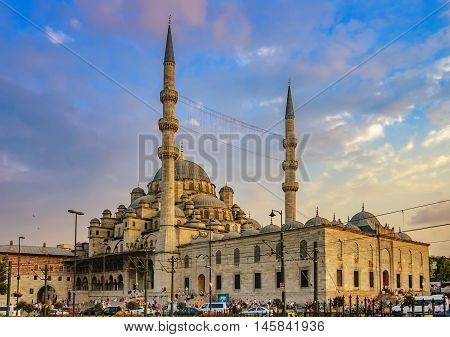 New mosque - Yeni Cami against the cloudy sky at sunset in Eminonu district of Istanbul Turkey