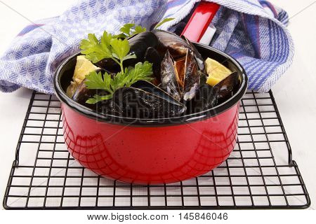 cooked scottish mussels with parsley and lemon in red enamel pot