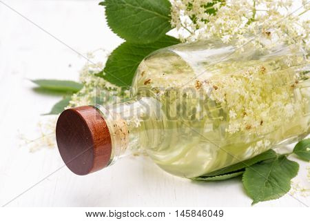 glass bottle with elderflower syrup on a white wooden background homemade for refreshing juice or champagne in summer selective focus narrow depth of field
