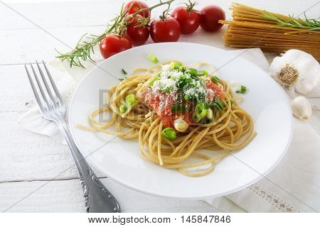 whole wheat spaghetti pasta with fresh tomato sauce and spring onions on white rustic wood and some ingredients in the background homemade vegetarian meal in a Mediterranean style selected soft focus narrow depth of field