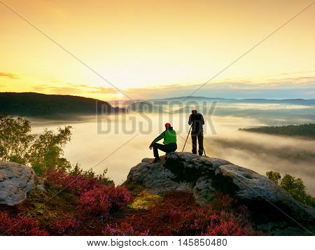 Hiker And Photo Enthusiast Stay With Tripod On Cliff And Takes Photos.