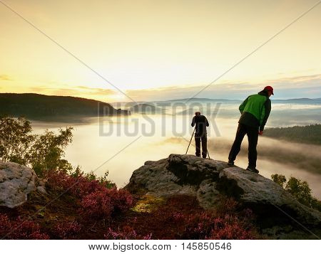 Hiker Look Down Into Fogy Valley. Photographer Stay On Cliff And Takes Photos.