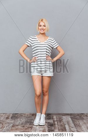 Full length of happy beauitful young woman standing and smiling over gray background